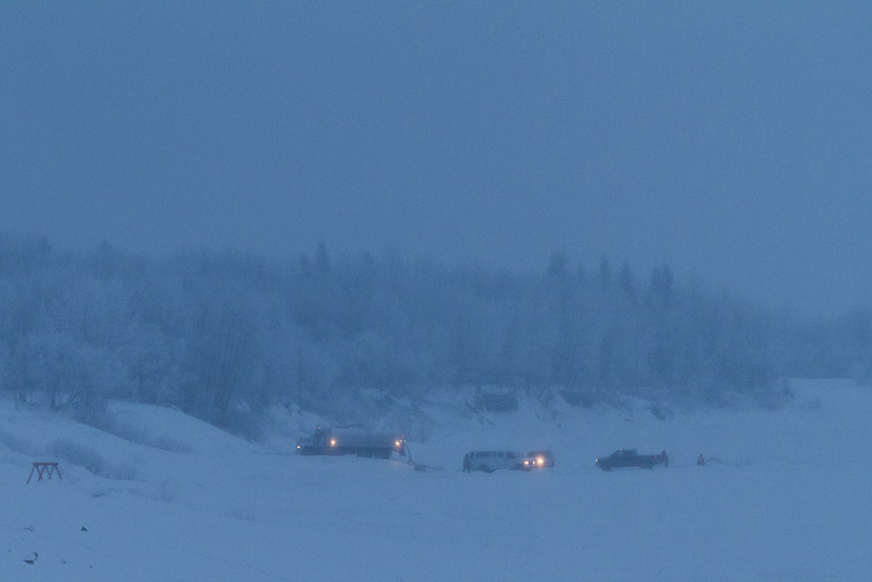 2011 January 15 before dawn on a cloudy morning: vehicles on the Moose River. Truck picking up water for winter road work.