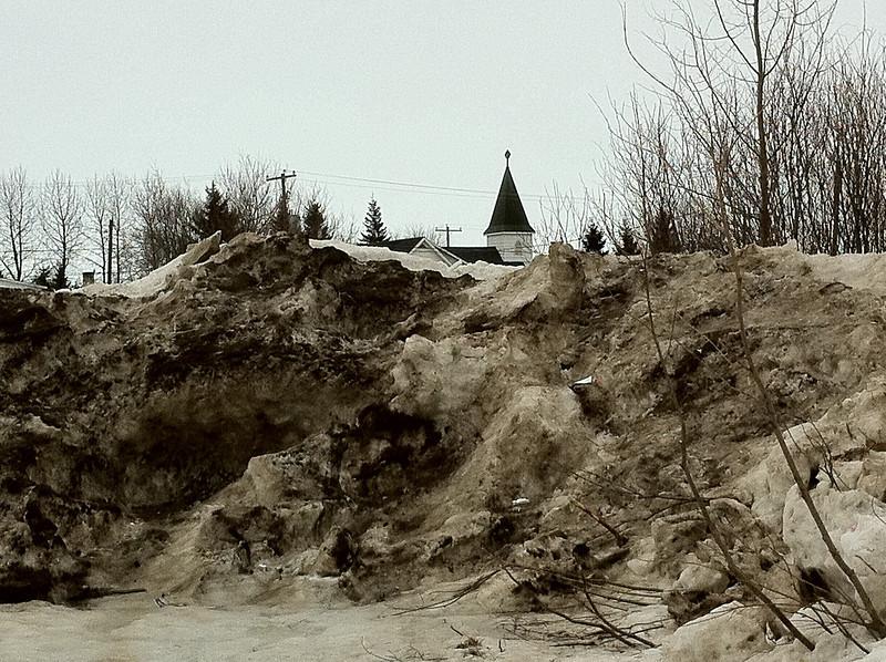 Church of the Apostles in Moosonee seen behind snow bank