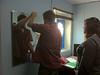 Articling student Brian O'Neill installing a mirror in office of Kathryn Culek, staff lawyer