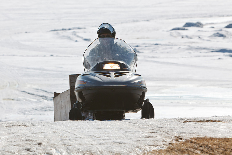 Snowmobile and sled coming up McCauley's Hill