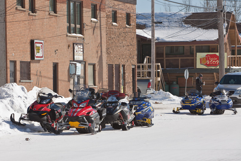 Snowmobiles outside Sky Ranch Restaurant on First Street in Moosonee 2011 March 6th.