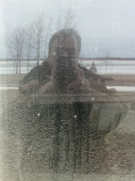 Paul, wearing Tough Duck parka reflection in office window.