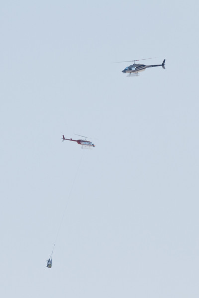 This is one of the times of the year when helicopters are used to sling loads to Moose Factory from Moosonee. Loaded slings hang down, empty runs trail behind the helicopters.