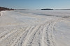Snowmobile tracks crossing the tide mark. Butler Island in the distance.