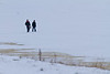 Two people walking on the Moose River.