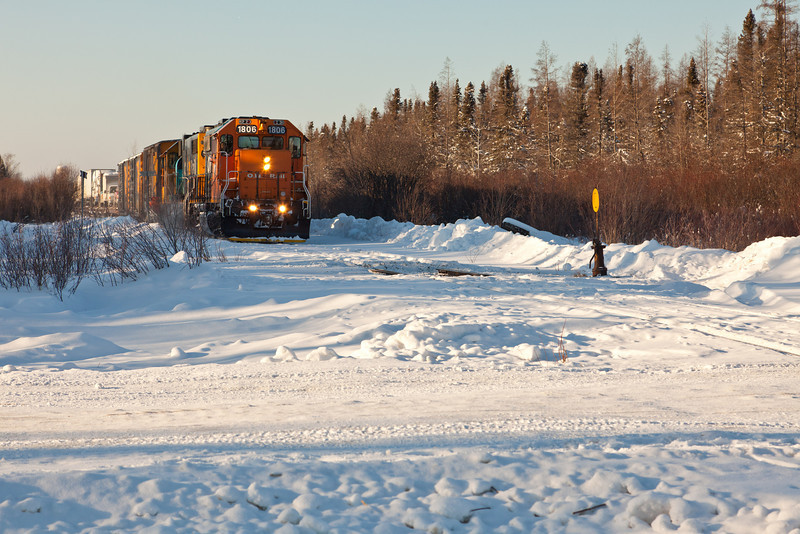 Ontario Northland Railway locomotives GP38-2's 1802 and 1806 with freight seen from winter road crossing as they pull forward to back onto the wye to access loading ramp on Airport Road. 2011 January 28th.