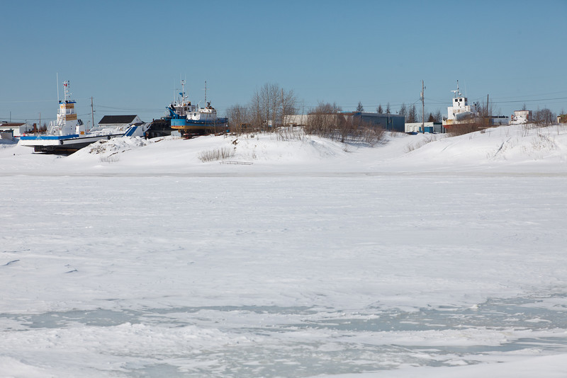 Tugs and barges in winter storage along the Moose River in Moosonee, Ontario.