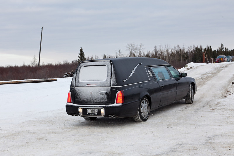 A new hearse for use in Moosonee and Moose Factory is unloaded from flatcars that arrived in Moosonee on the Polar Bear Express.