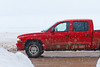 Red truck on Revillon Road in snow storm.