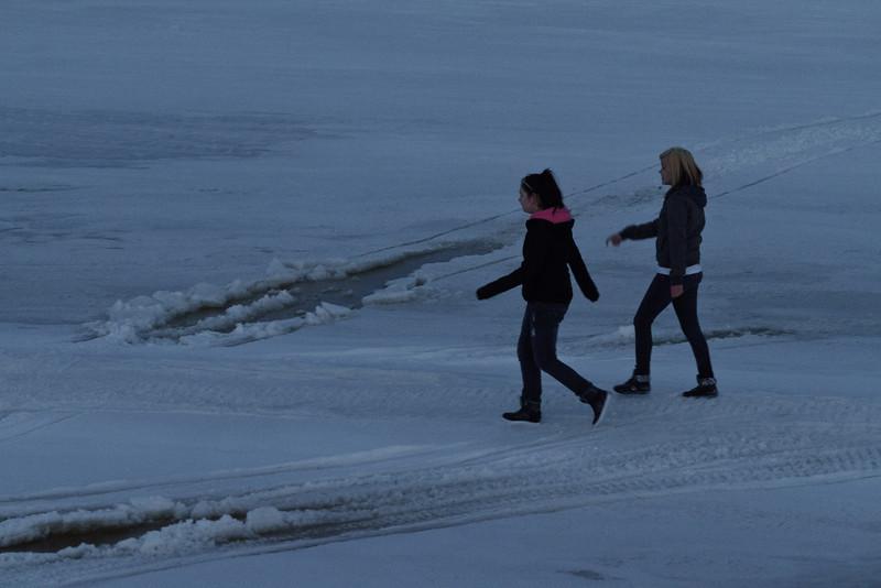 Two people walking on the river near Moosonee.