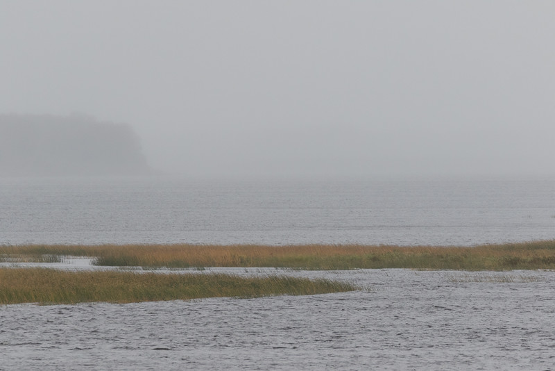 Looking up the Moose River from Moosonee with light rain in the distance.