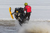 Snowmobile running through surface water.