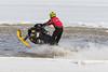 Snowmoible running through surface water.