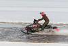 Snowmobile running through surface water on the Moose River.