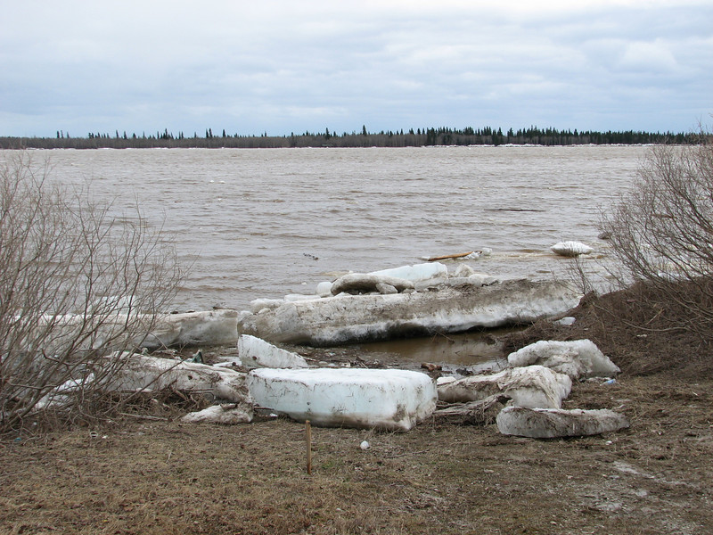 Stranded floes near Moosonee Pentecostal Church- stake in left foreground shows high water mark