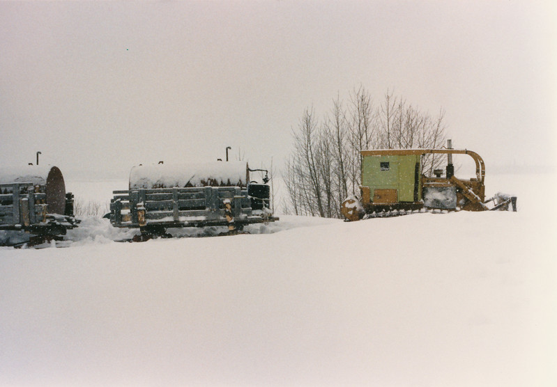 Bulldozer and two sleds of tractor train. Moosonee 1980s.