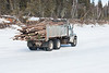 Innlink Concrete Limited dump truck carrying logs on the winter road to Moose Factory from Moosonee.