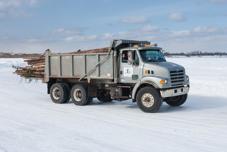 Innlink Concrete Limited dump truck carrying logs on the winter road to Moose Factory from Moosonee. Passenger holding up a can of Coca Cola.