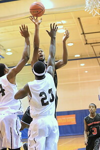 Malik Price-Martin shoots over two Rock defenders