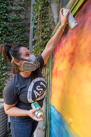 Mollie Graybeal puts some finishing touches on a seascape mural she painted in the alley. Fran Ruchalski   Pharos-Tribune