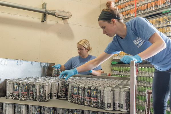 Ashlyn Brown, left, and Aylssa McPherson stack cans on skids for transport to the breweries to be filled with beer. Fran Ruchalski | Pharos-Tribune