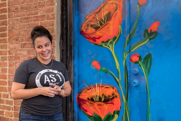 Mollie Graybeal explains some of the techniques and details that went in to the painting of this mural on the rear door of her family's furniture business.  Fran Ruchalski | Pharos-Tribune