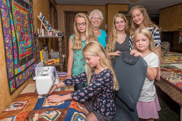 Featured quilter at the Carroll County Harvest of Quilts show, Sue Hodge, center, is surrounded by five of her granddaughters who also have a passion for quilting. The Hurst sisters are Adrianna, 11 (seated at the sewing machine), Donna, 13 (from left), Miriam, 7, Justine, 17, Anabel, 14, and Miriam, 7. They are the fifth generation to be involved in quilting. Fran Ruchalski   Pharos-Tribune