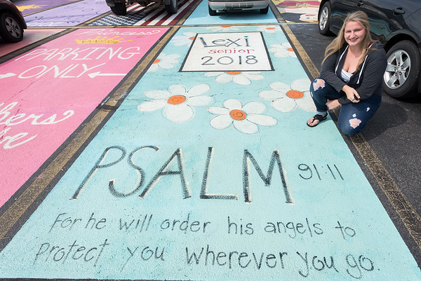 Pioneer senior Lexi Baker poses next to her personally painted parking place at the school on Monday afternoon. About 30 seniors painted their own parking places as part of a fundraising program at the school. Fran Ruchalski   Pharos-Tribune