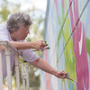 Logansport artist Teri Partridge, co-owner of Pear Tree Gallery, paints a mural outside the windows of Logansport Memorial Hospital's soon-to-be-completed cancer care center. Fran Ruchalski | Pharos-Tribune