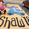 Pioneer senior Alyssa Shaw poses next to her personally painted parking place at the school on Monday afternoon. About 30 seniors painted their own parking places as part of a fundraising program at the school. Fran Ruchalski | Pharos-Tribune