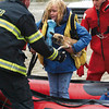 Alexis Doss and her dog Emiley is helped from a rescue boat by Cass County Fire District 1's Steve Crispen.