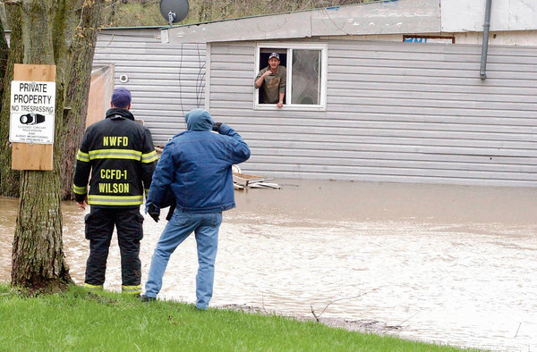 Alan Doss talks to personel before being rescued from his flooded home on Co. Rd. 50S near 250W.