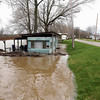 A trailer along County Road 50 South is surrounded by flood waters of the Wabash River Friday.