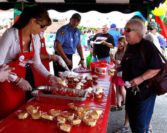 P-T photos | Steve Summers <br /> BIG SCOOPS: Nicole Stottler dishes out bowl after bowl of strawberries and shortcake during Celebrate Logansport Day Thursday.
