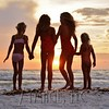 Four girls frolicking on the beach at sunset.