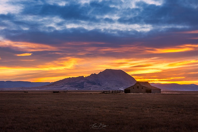 Sunset at Bear Butte. A popular abandoned barn of Western South Dakota on the foreground.