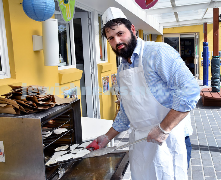 Matzah Bakery at Moriah Early Learning Centre. Rabbi Elimelech Levy placing a tray of Matzahs into the oven. Pic Noel Kessel