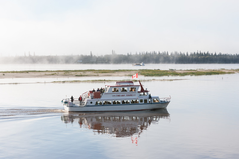 Polar Princess tour boat in foreground with barge Manitou Island II carrying school bus on far side of sandbar. Fog lifting.