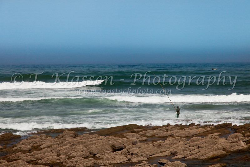A fisherman with ocean waves on the Corniche in Casablanca, Morocco.