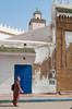 Arches and doorway with street activity in the souqs of Essaouira, Morocco.