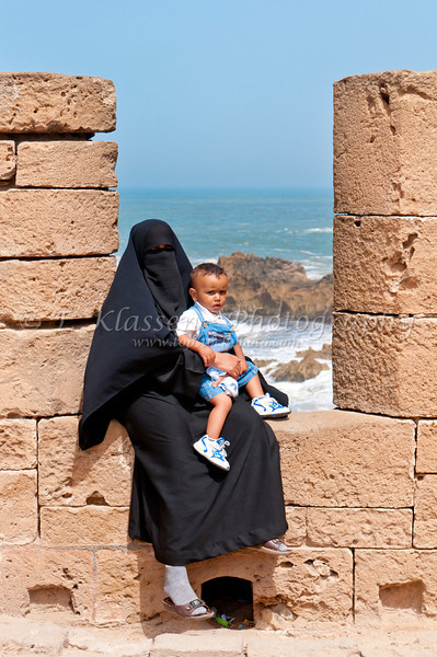 Arab woman in niqab and child at the Portuguese fort of Mogador in Essaouira, Morocco.