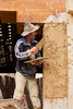 A construction worker repairing a plaster wall in the Medina of Fes, Morocco.