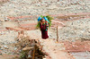 A Berber woman carrying straw crossing a bridge over the Ourika River in the Ourika Valley, Morocco.