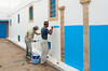 Workers paint a wall in the Oudayas Casbah in Rabat, Morocco.
