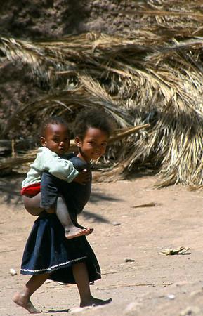 MOROCCO 2003/011 Oulad Driss.  In Marokko is 70% van de bevolking jonger dan 30 jaar. 40% van de mannelijke en 66% van de vrouwelijke bevolking is analfabeet. Er bestaat een leerplicht, maar daar wordt nog minder rekening mee gehouden dan met de snelheidsbeperkingen op de Belgische autowegen. Er is geen enkele controle, met als gevolg dat zich meer kinderen bevinden op straat en op de akkers dan in de klaslokalen. De toekomst van het land ziet er huiveringwekkend uit.