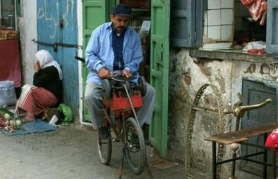 MOROCCO 2003/ 022 Tetouane. Een slijper aan 't werk.  In Marokko is 70% van de bevolking jonger dan 30 jaar. 40% van de mannelijke en 66% van de vrouwelijke bevolking is analfabeet. Er bestaat een leerplicht, maar daar wordt nog minder rekening mee gehouden dan met de snelheidsbeperkingen op de Belgische autowegen. Er is geen enkele controle, met als gevolg dat zich meer kinderen bevinden op straat en op de akkers dan in de klaslokalen. De toekomst van het land ziet er huiveringwekkend uit.