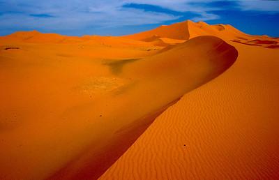 """MOROCCO 2003/ 014 De zandduinen in de omgeving van Merzouga bereiken een hoogte van meer dan 100 meter. Door de felle wind die hier soms opsteekt, veranderen ze voortdurend van vorm. Ook de kleur van het zand verandert, al naar gelang de invalshoek van de zonnestralen. Bijna overal waar we in goed bereikbare woestijnoases toekwamen, vroeg men ons naar kleren die we niet meer droegen of versleten potten en pannen. Het was opvallend dat die vraag altijd gesteld werd door verkopers van tapijten of handwerk. Deze mensen zagen er telkens zo welgesteld uit, dat we ons niet konden voorstellen dat ze deze zaken echt nodig hadden. Toen we om uitleg vroegen, kregen we het volgende te horen: """" In de wintertijd, wanneer de Sahara wat toegankelijker wordt, trekt men met een 4x4 de woestijn in, op zoek naar de Nomaden die zich vaak op erg geïsolleerde plaatsen hebben teruggetrokken en in lompen gekleed gaan."""" """"Zouden we te maken hebben met een altruïst?"""", vragen we ons af. Neen, zo blijkt. De nomaden verhandelen sieraden en artisanaal werk, en omdat ze zelden in bewoond gebied komen, en niets kunnen aanvangen met geld, drijven ze ruilhandel. Met het waardeloze materiaal, geschonken door de toeristen, geraakt deze man aan juwelen en tapijten, die hij verkoopt aan andere toeristen."""