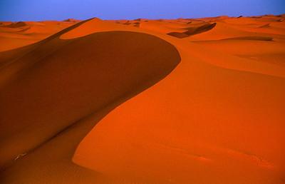 """MOROCCO 2003/ 015 De zandduinen in de omgeving van Merzouga bereiken een hoogte van meer dan 100 meter. Door de felle wind die hier soms opsteekt, veranderen ze voortdurend van vorm. Ook de kleur van het zand verandert, al naar gelang de invalshoek van de zonnestralen. Bijna overal waar we in goed bereikbare woestijnoases toekwamen, vroeg men ons naar kleren die we niet meer droegen of versleten potten en pannen. Het was opvallend dat die vraag altijd gesteld werd door verkopers van tapijten of handwerk. Deze mensen zagen er telkens zo welgesteld uit, dat we ons niet konden voorstellen dat ze deze zaken echt nodig hadden. Toen we om uitleg vroegen, kregen we het volgende te horen: """" In de wintertijd, wanneer de Sahara wat toegankelijker wordt, trekt men met een 4x4 de woestijn in, op zoek naar de Nomaden die zich vaak op erg geïsolleerde plaatsen hebben teruggetrokken en in lompen gekleed gaan."""" """"Zouden we te maken hebben met een altruïst?"""", vragen we ons af. Neen, zo blijkt. De nomaden verhandelen sieraden en artisanaal werk, en omdat ze zelden in bewoond gebied komen, en niets kunnen aanvangen met geld, drijven ze ruilhandel. Met het waardeloze materiaal, geschonken door de toeristen, geraakt deze man aan juwelen en tapijten, die hij verkoopt aan andere toeristen."""