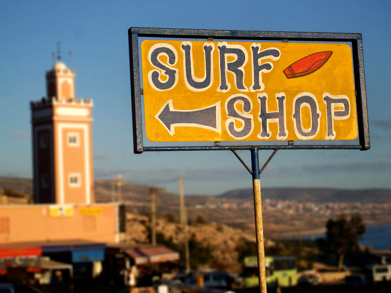 Surf shop sign and minaret in Taghazout. 2007.