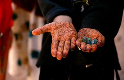 MOROCCO 2003/ 010 Fes.  In Marokko is 70% van de bevolking jonger dan 30 jaar. 40% van de mannelijke en 66% van de vrouwelijke bevolking is analfabeet. Er bestaat een leerplicht, maar daar wordt nog minder rekening mee gehouden dan met de snelheidsbeperkingen op de Belgische autowegen. Er is geen enkele controle, met als gevolg dat zich meer kinderen bevinden op straat en op de akkers dan in de klaslokalen. De toekomst van het land ziet er huiveringwekkend uit. 't Beschilderen van handen met henna is hier een traditie.